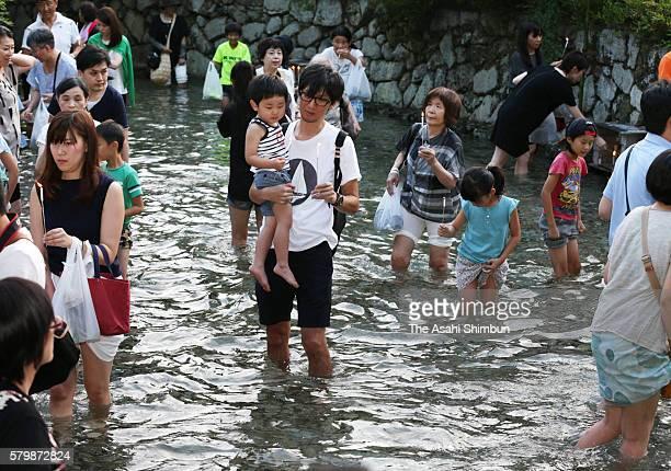 People bathe their feet to the Mitarashi pond holding candles during the Mitarashi Festival at Shimogamo Shrine on July 23 2016 in Kyoto Japan...