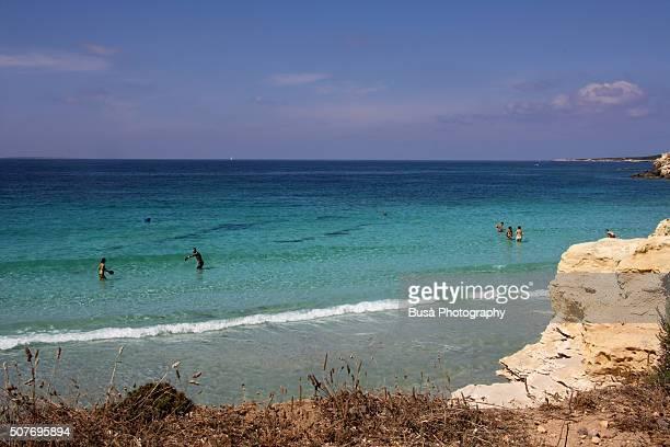 people bathing and playing on the beach in the bay of cala su pallosu, sardinia, italy - oristano imagens e fotografias de stock