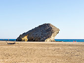 People bathing and sunbathing on the beach. Rocky coast of the Cabo de Gata with formations of volcanic rock of black color and beach of sand of brown color. Cabo de Gata - Nijar Natural Park, Cala de Monsul, Almeria, Andalusia, Spain.