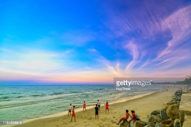 mensen baden, sporten op prachtige stranden bij zonsondergang - quảng ngãi stockfoto's en -beelden