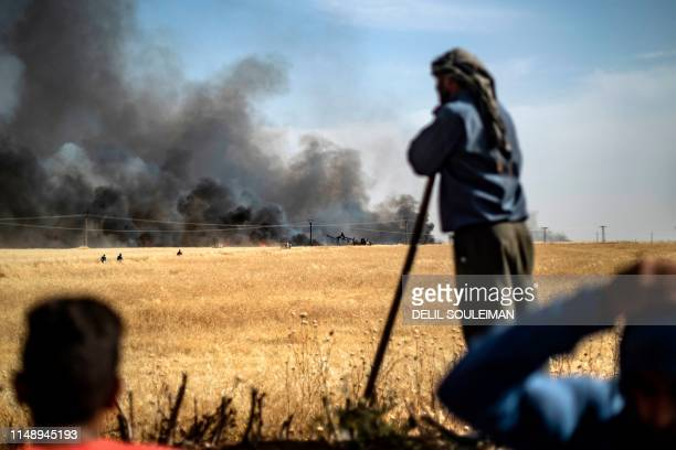 People battle a blaze in an agricultural field in the town of alQahtaniyah in the Hasakeh province near the SyrianTurkish border on June 10 2019...