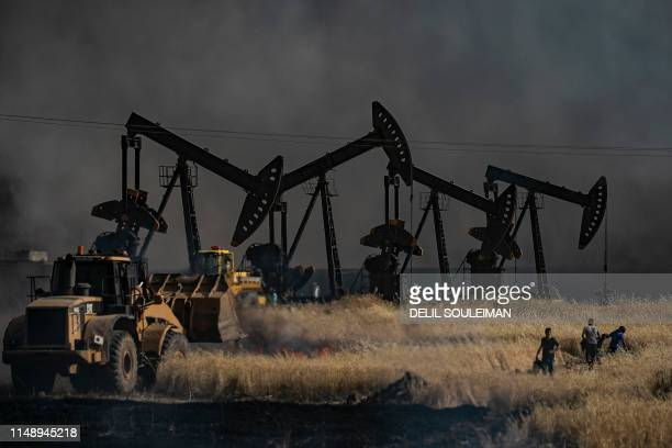 TOPSHOT People battle a blaze next to an oil well in an agricultural field in the town of alQahtaniyah in the Hasakeh province near the SyrianTurkish...