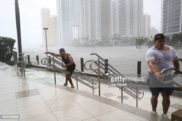 People battle high winds and rain to take in the sights along the Miami River which is flooding as Hurricane Irma passes through on September 10 2017...