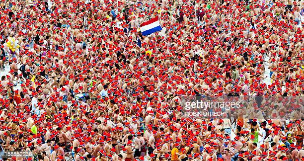 People bearing colors ot the Dutch national flag take a bath in the North Sea during the Nieuwjaarsduik on New Year's Day in Scheveningen on January...