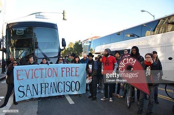 People behind a Eviction Free San Francisco banner block an Apple bus as a Google bus passes on Valencia St. The protest called for a moratorium on...