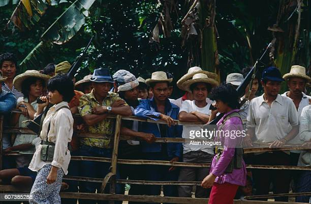 People behind a wooden fence look on as guerilla fighters armed with machine guns pass in front of them at the New People's Army secret base camp  ...