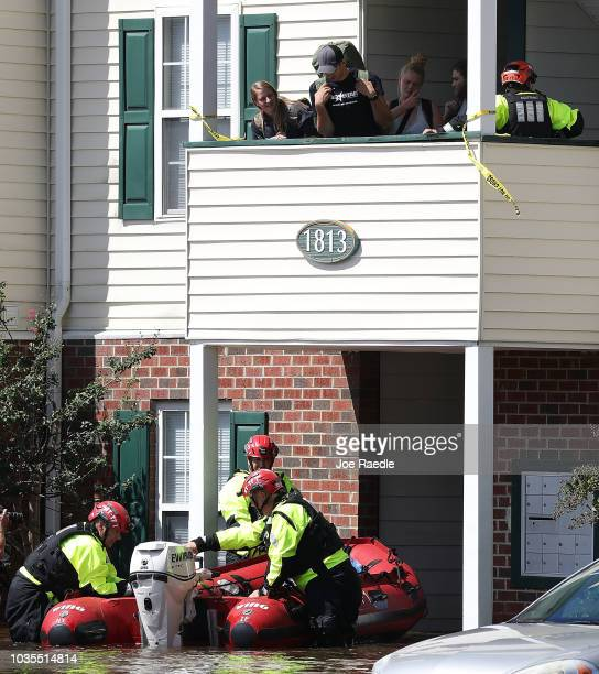 People being evacuated wait for members of New York Urban Search and Rescue Task Force One to position their rescue boat in an area flooded with...