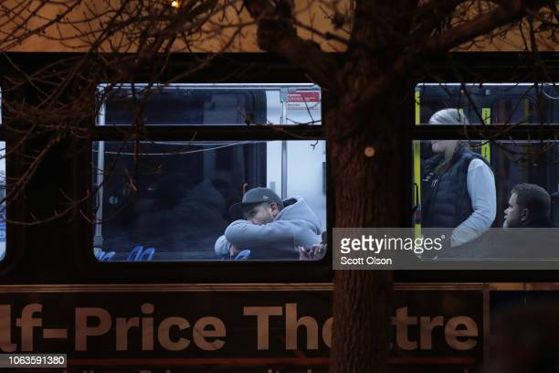 People believed to be Mercy Hospital workers wait on city buses outside after a gunman opened fire at Mercy Hospital on November 19 2018 in Chicago...