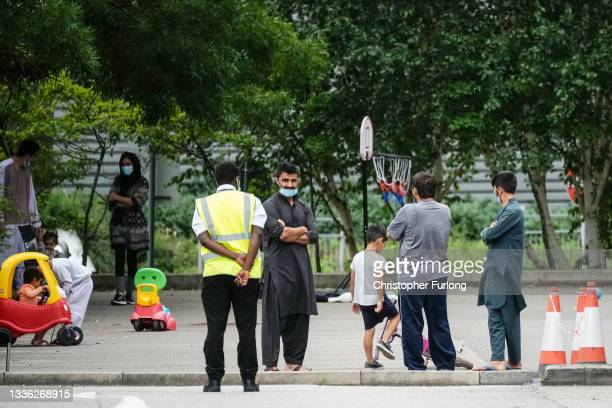 People believed to have recently arrived from Afghanistan stand in the courtyard of a hotel near Manchester Airport on August 25, 2021 in Manchester,...