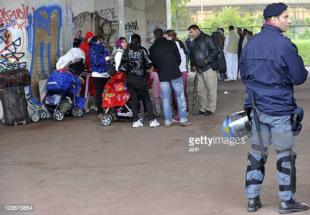People belonging to the Roma community gather in front of Italian Police as local authorities evacuate caravans from their camp site situated in the...