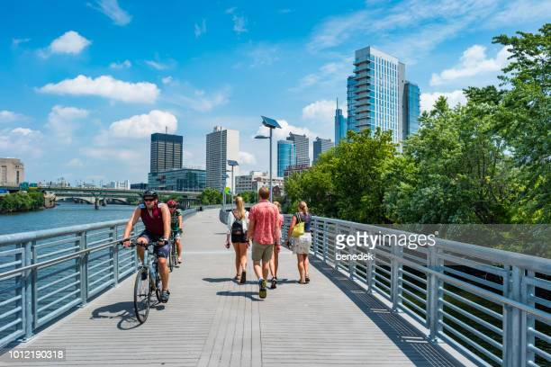 people bike and walk on the schuylkill banks boardwalk in philadelphia usa - promenade stock pictures, royalty-free photos & images