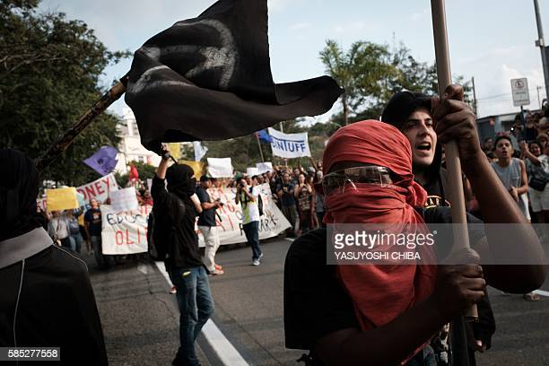 TOPSHOT People block a road during a protest against the Olympic torch relay for Rio 2016 Olympic Games in Niteroi on August 2 2016 / AFP / YASUYOSHI...