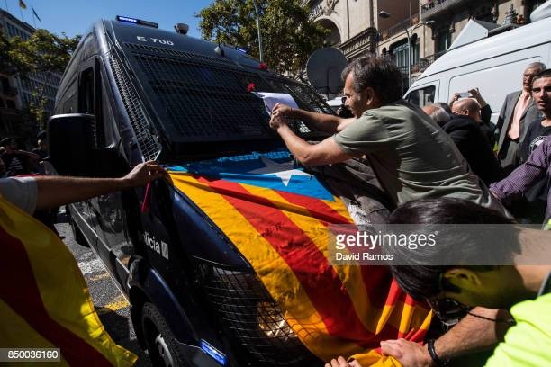 People block the road a Catalan Autonomous Police van outside the Catalan VicePresident and Economy office as police officers holds a searching...