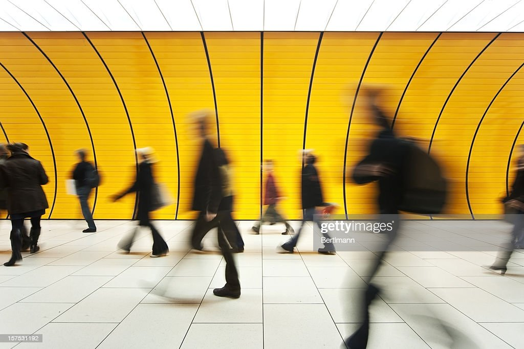 People blurry in motion in yellow tunnel down hallway : Stock Photo