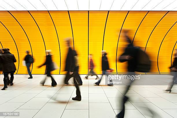 people blurry in motion in yellow tunnel down hallway - dringendheid stockfoto's en -beelden