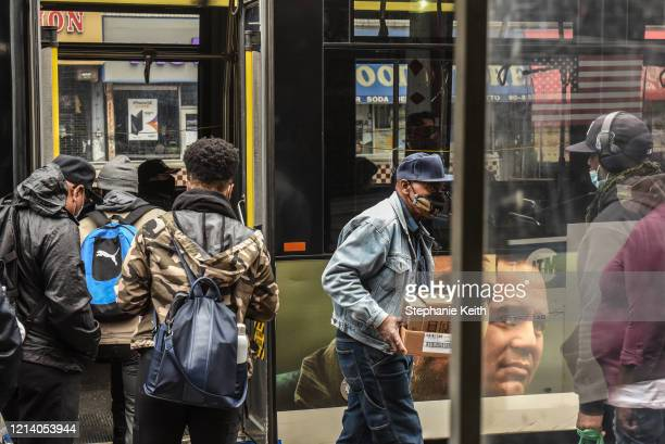 People board a bus on May 19, 2020 in the Jamaica neighborhood in the Queens borough in New York City. New York City is currently in its ninth week...