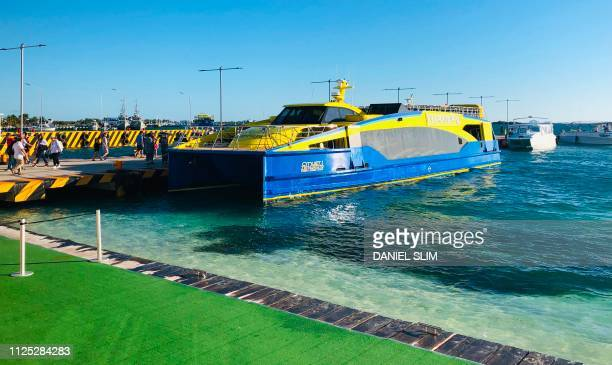 People board a ferry back to Cancun in Isla Mujeres Quintana Roo State Mexico on February 16 2019 Playa del Carmen and Cancun are the top tourist...