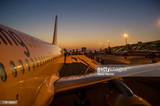 People board a Vueling plane heading to Ibiza at the BarcelonaEL Prat airport on August 21 2013 in Barcelona Spain The small island of Ibiza lies...