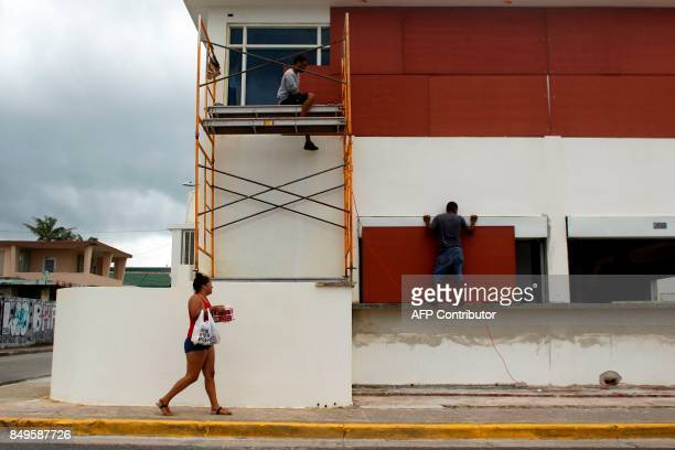 People board up windows of a business in preparation for Hurricane Maria in Luquillo Puerto Rico on September 19 2017 Maria headed towards the Virgin...
