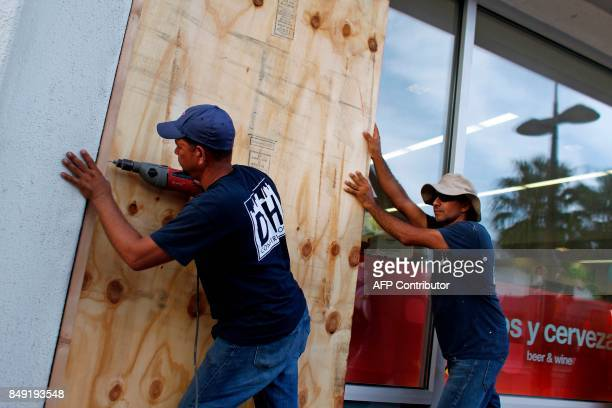 People board up windows of a business in preparation for the anticipated arrival of Hurricane Maria in San Juan Puerto Rico on September 18 2017...