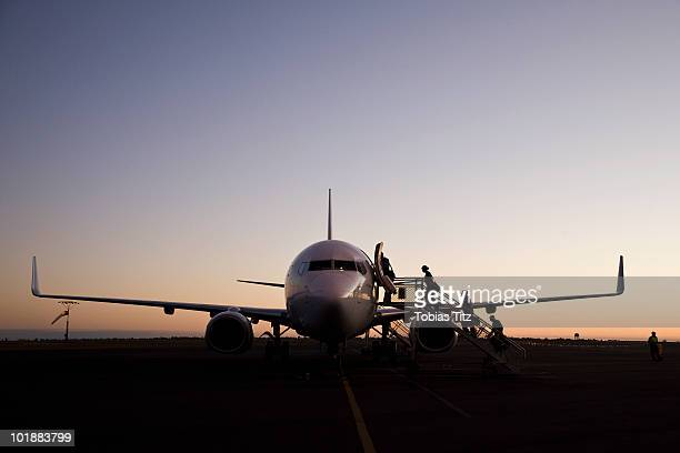 People boarding an airplane at dusk,  Port Hedland, Western Australia, Australia