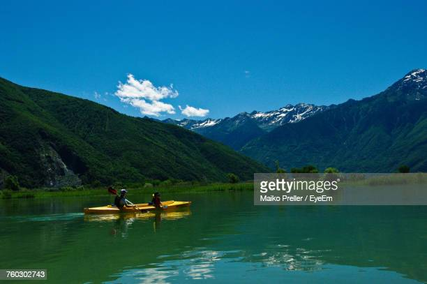 People Boating On Lake Against Mountains