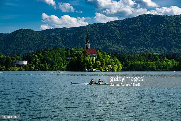 People Boating On Lake Bled Against Church And Tree Mountain