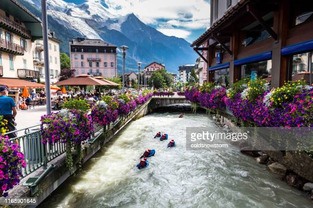 people bodyboarding in river rapids in charming mountain resort of chamonix, france - chamonix stock pictures, royalty-free photos & images