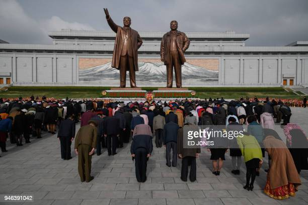 TOPSHOT People bow as they pay their respects before the statues of late North Korean leaders Kim Il Sung and Kim Jong Il at Mansu hill in Pyongyang...