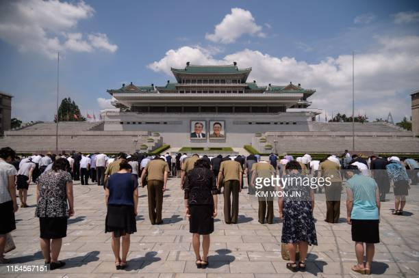 People bow before the portraits of late North Korean leaders Kim Il Sung and Kim Jong Il as the country marks the 25th death anniversary of Kim Il...