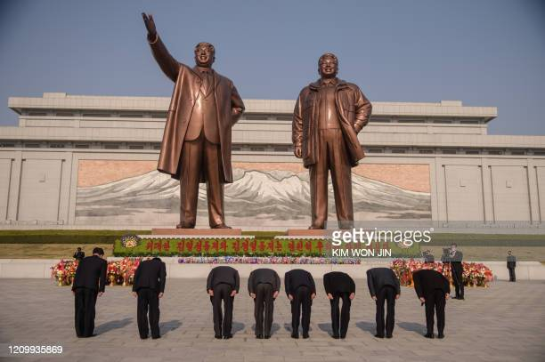 People bow before the statues of late North Korean leaders Kim Il Sung and Kim Jong Il on the occasion of the 108th birthday of late North Korean...