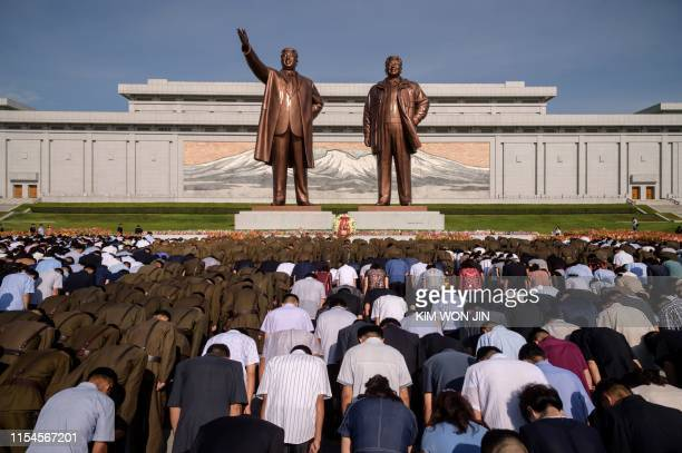 People bow before the statues of the late North Korean leaders Kim Il Sung and Kim Jong Il as the country marks the 25th death anniversary of Kim Il...