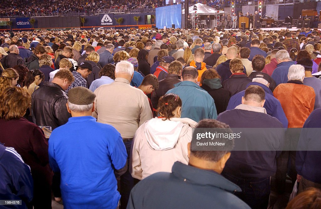 People bow their heads in prayer as they come forth to 'accept Jesus Christ' during the last California mission for America's best known evangelist, 84-year-old Billy Graham, on May 8, 2003 in San Diego, California. Some 54,000 people attended tonight's service which is expected to total 200,000 over the four-night event as thousands convert to Christianity.