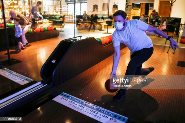 People bowl at All Star Lanes bowling alley at Westfield in White City on August 15, 2020 in London, England. Theatres, casinos and bowling alleys...