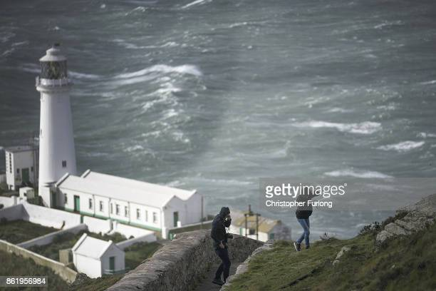 People brace themselves against the wind of Hurricane Ophelia next to South Stack Lighthouse on October 16 2017 in Holyhead Wales Hurricane Ophelia...