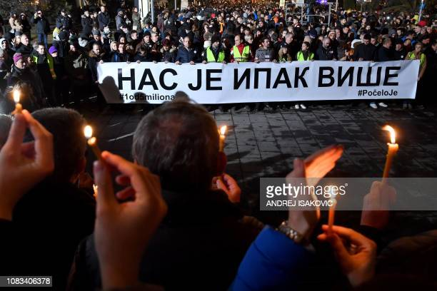 People brandish candles as others hold a banner reading in cyrillic Still there is more of us during a silent march in Belgrade in memory of Serb...