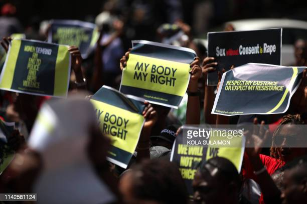 TOPSHOT People brandish placards during a protest to challenge impunity and genderbased discrimination raids on women by Federal Capital Territory...