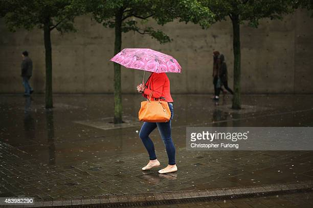 People brave a downpour in Manchester City centre on August 14, 2015 in Manchester, England. Heavy rain and flood warnings have been issued by the...