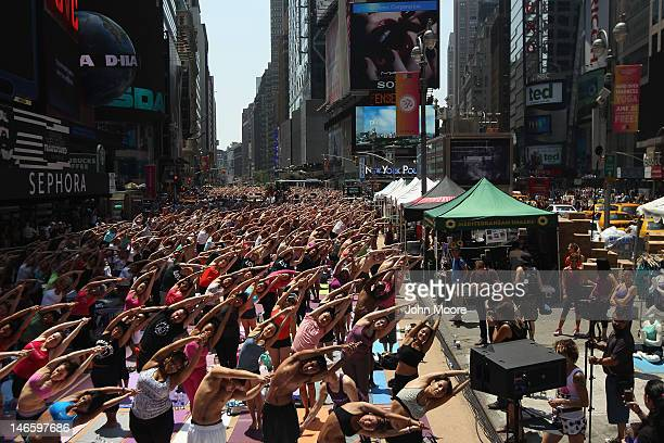 People brave high temperatures while practicing bikram yoga as part of the annual Mind Over Madness event in Times Square on June 20 2012 in New York...