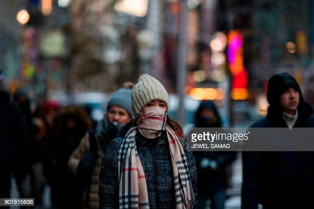 People brave the cold weather as they take a morning stroll around Times Square in New York on January 5 2018 The National Weather Service said early...