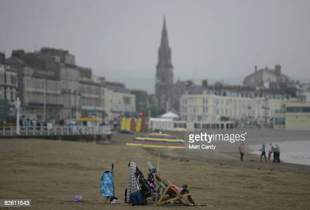 People brave the gloomy weather at Weymouth seafront on August 31 2008 in Weymouth England Forecasters have claimed that this August has been one of...