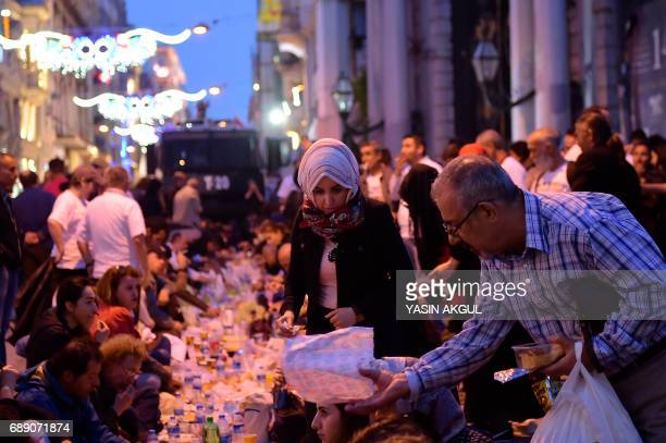 People break their fast while police with water cannons patrol nearby on May 27 2017 near Taksim Square in Istanbul during the first day of the holy...