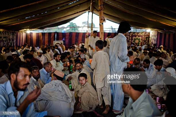People break their fast with a donated free meal at 'Iftar' on the second day of the holy month of Ramadan on August 3 2011 in Islamabad Pakistan...