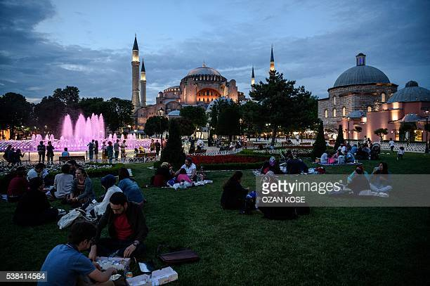 People break their fasting on June 6 2016 as they eat sitting on the grass at the Blue Mosque square in Istanbul during the first day of the holy...