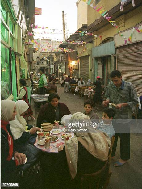 People breaking the fast by eating in the streets and on sidewalks during the month of Ramadan