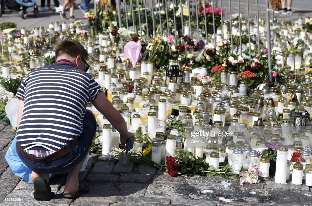 People bring candles and flowers to the makeshift memorial for the victims of the stabbings at the Turku Market Square, Finland on August 20, 2017. Two people were killed and six were injured in a stabbing spree in the Finnish city of Turku on August 18, 2017, police said, after officers shot one suspect and warned several others could still be at large. / AFP PHOTO / Lehtikuva / Vesa Moilanen / Finland OUT
