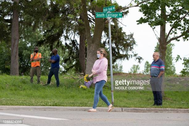People bring flowers and pay their respects at the scene where a man driving a pickup truck struck and killed four members of a Muslim family in...