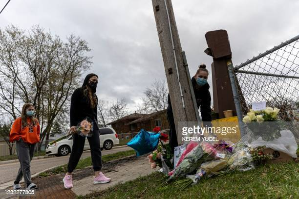 People bring flowers and signs during a vigil where Daunte Wright was shot and killed by a police officer in Brooklyn Center, Minnesota on April 12,...