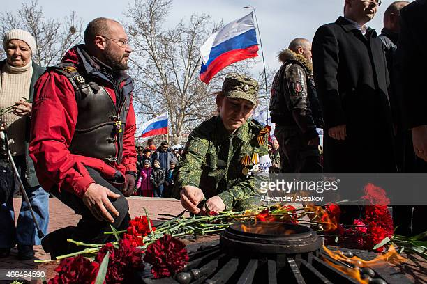 People bring flowers to the eternal flame at the memorial of the heroic defense of Sevastopol as Crimeans celebrate the first anniversary of the...