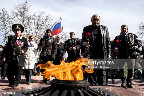 People bring flowers to the eternal flame on the memorial of the heroic defense of Sevastopol as Crimeans celebrate the first anniversary of the...